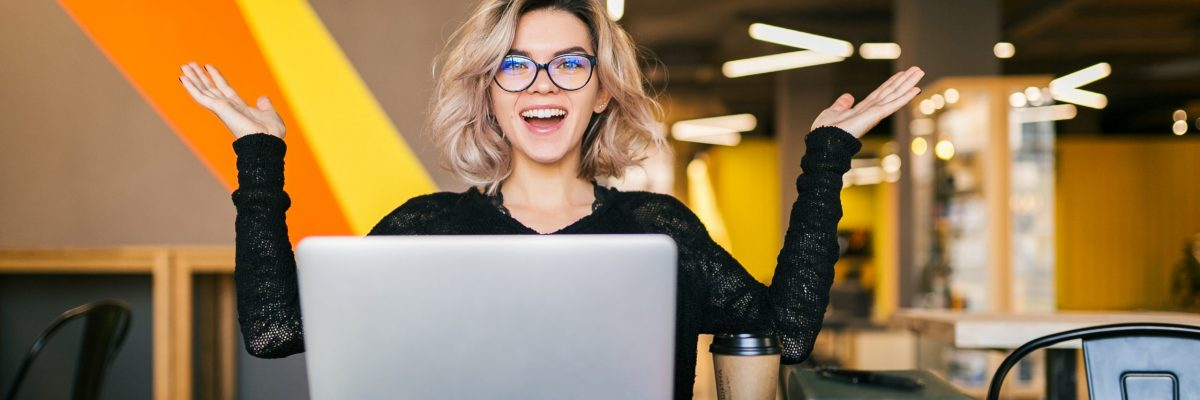 funny happy excited young pretty woman sitting at table in black shirt working on laptop in co-working office, wearing glasses